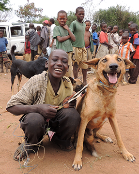 A happy boy holds his dog on a leash while other boys look on.